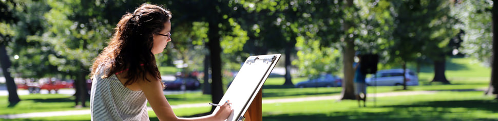 Female Student Drawing on Art Easel on Campus Front Lawn