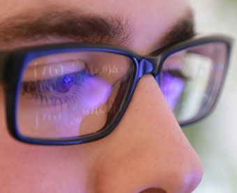 Photo of Student With Code Reflecting in Reading Glasses