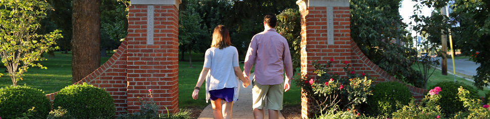 Alumni Holding Hands walking Through the Campus Front Lawn