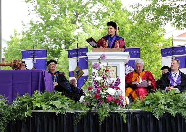 Dr. Nichole DeWall, associate professor of English at McKendree University, addresses the crowd at the 2018 McKendree commencement ceremony as winner of the Grandy Faculty Award. Looking on, left to right, is Dr. Christine Bahr, provost and Dean; Dr. James Dennis, university president;  and Daniel Lett, president of the board of trustees.