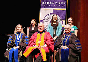 Division of Science and Mathematics honorees Kristyn Tully '19 (mathematics), Ashley Hathaway '19 (biology) and Brittni Futrell '19 (biopsychology) are joined on the stage by (seated) Dr. Michele Schutzenhofer '03, division chair; President James Dennis; and Dr. Christine Bahr, provost and dean.