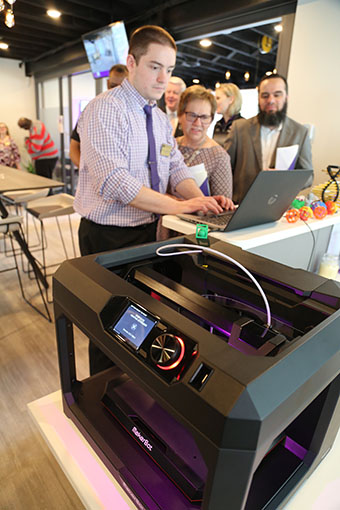 Jonathan Ciembronowicz '15, systems analyst, demonstrates 3-D printing capabilities to Dr. Janice Wiegmann, professor of nursing, and Dr. Ahed Elmsallati, assistant professor of computing.