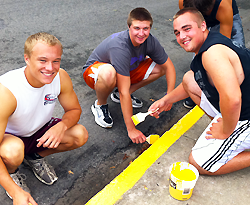 Students painting street curb