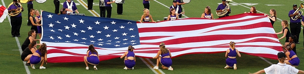 Photo of American Flag on Leemon Field held by the McK Dance Team and the PomCats
