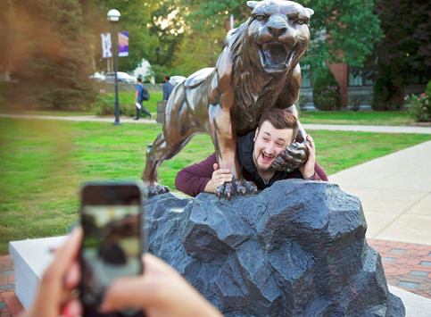 Student Taking a Photo Bearcat Statue