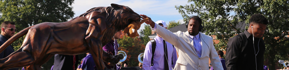 Male Student Rubbing the Nose of the Bearcat Statue