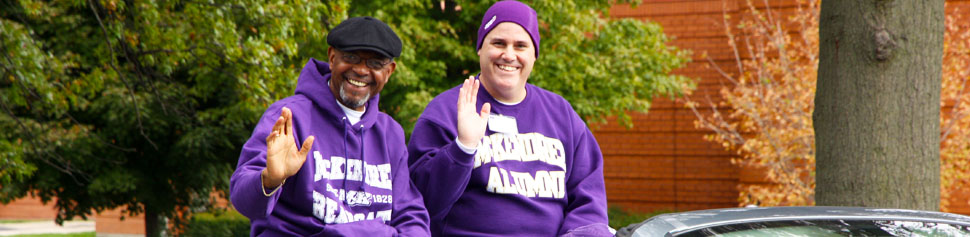 Two Male Alumni Waving Hands at Homecoming Parade